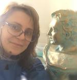 Stefania Maranzano, artista artigiana, nel suo laboratorio, sorride davanti a una scultura realizzata da lei